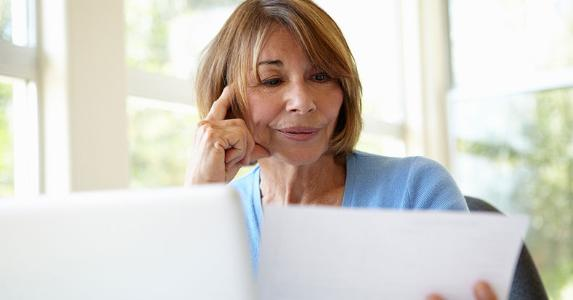Senior woman looking at her paperwork © iStock