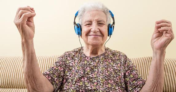 Senior woman wearing blue headphones | berna namoglu/Getty Images