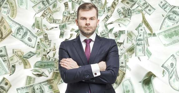 Serious businessman standing with money in the background © iStock