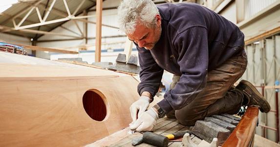 Ship builder shaving wood planks | Kelvin Murray/Getty Images