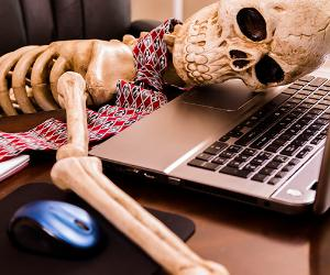 Skeleton slumped on notebook computer in office