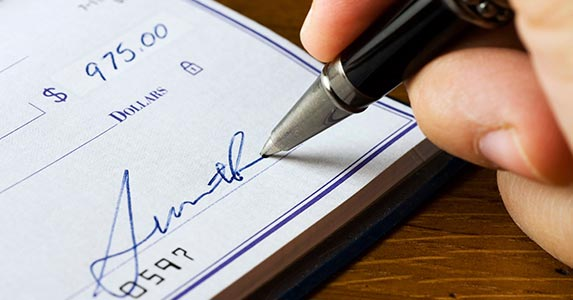 Signing someone else's name on a check | bluestocking/E+/Getty Images