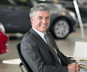 Smiling car salesman sitting in showroom © iStock