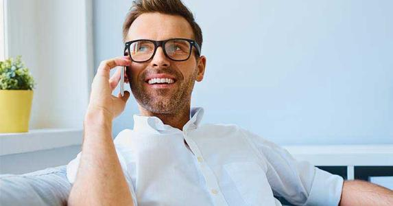Smiling man wearing glasses on a phone call © baranq/Shutterstock.com