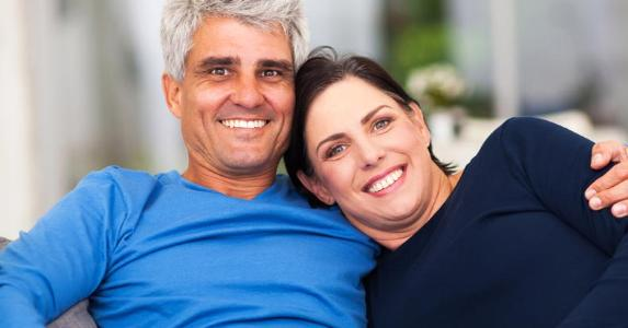 Smiling middle-aged couple sitting on a couch © michaeljung/Shutterstock.com