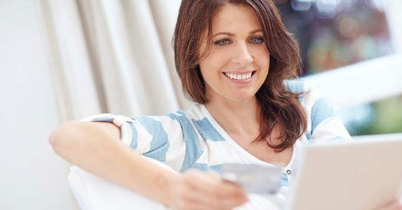 Smiling woman holding credit card and paperwork © iStock