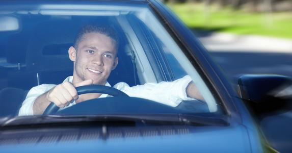 Smiling young man driving his car © LuckyImages/Shutterstock.com