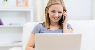 Woman talking on phone with laptop © wavebreakmedia/Shutterstock.com
