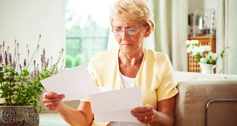 Solemn senior woman reading paperwork in living room | iStock.com/Izabela Habur