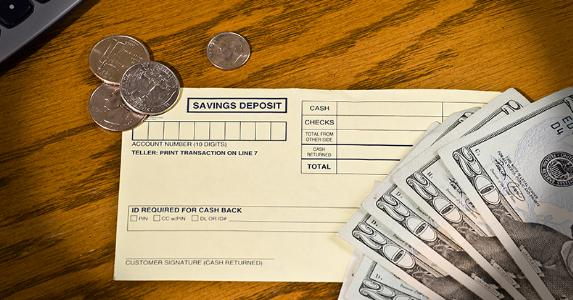 Some cash and a savings deposit slip © iStock