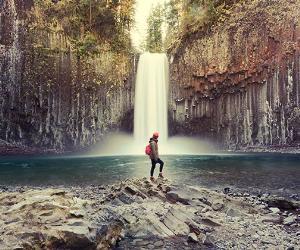 Woman standing by waterfall | Peerasith Patrick Triratpadoongphol/Shutterstock.com