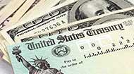 Tax refund check on top of hundred dollar bills © cabania/Shutterstock.com