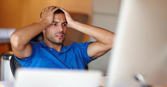 Stressed man staring at computer © iStock