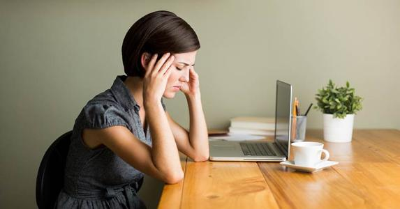 Stressed woman with a headache in home office | iStock.com/Aldo Murillo