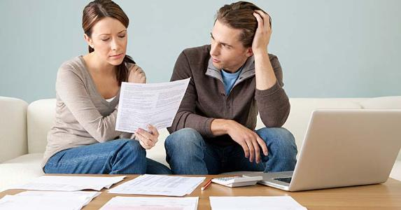 Stressed young couple going over paperwork and bills | Image Source/Getty Images
