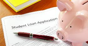 Student loan application piggy bank on desk  zimmytws/Shutterstock.com