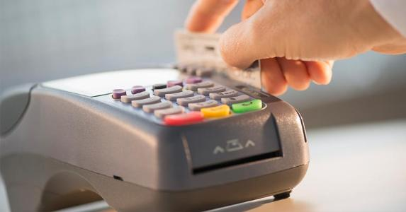 Swiping card through chip reader | Tetra Images/Getty Images