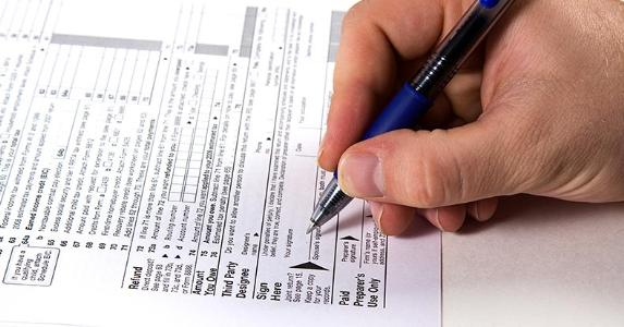 Male hand signing tax form with blue pen © Mehmet Dilsiz / Fotolia