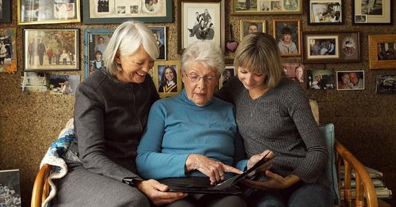 Three generations looking at photo album | LWA/Getty Images