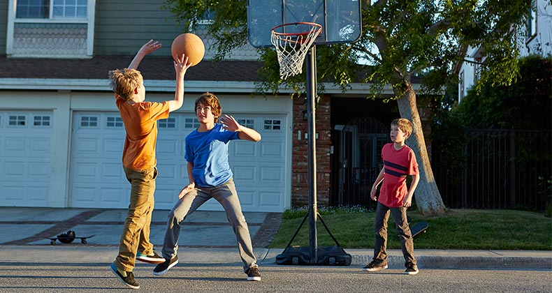 Three kids playing basketball in the street | Tony Garcia/Getty Images