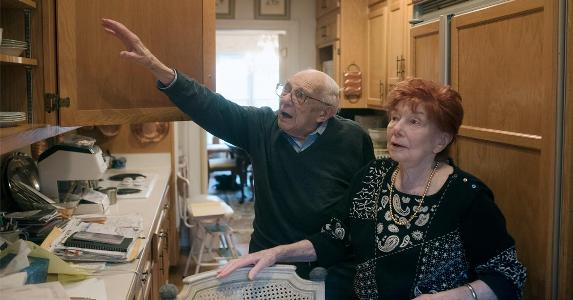 Older couple reaching into kitchen cabinets | The Washington Post/Getty Images