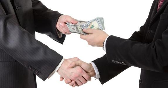 Businessmen exchanging money over deal © iStock