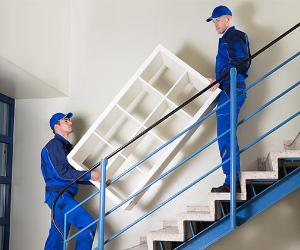 Two men moving a bookshelf up the stairs | Andrey_Popov/Getty Images