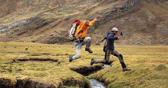 Two people jumping a small creek, outdoors © Mikadun/Shutterstock.com
