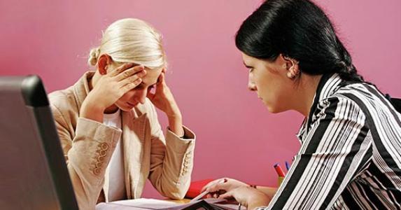 Two upset women doing paperwork @Bartosz Ostrowski/Shutterstock.com