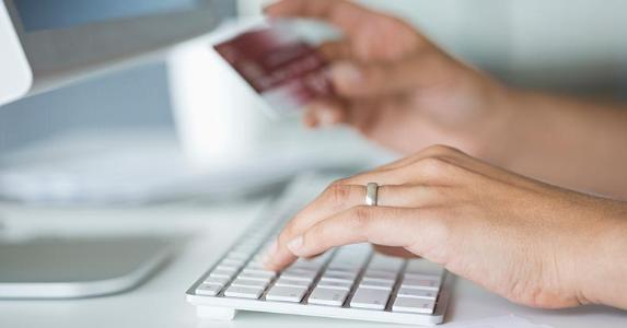 Typing credit card number to computer | Hero Images/Getty Images