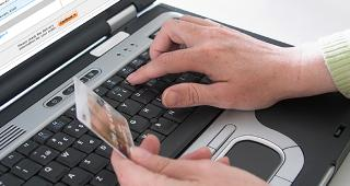 Online purchase with credit card © Ingvald Kaldhussater/Shutterstock.com