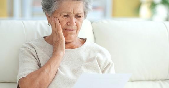 Upset elderly woman reading a letter | iStock.com