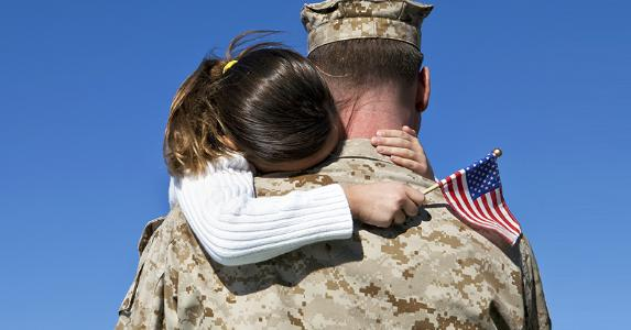 Veteran holding young girl