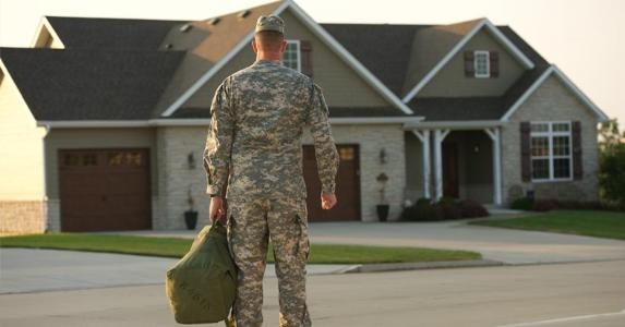Veteran standing with bag outside of home | Veterans United