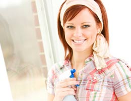 Smiling woman holding a bottle spray