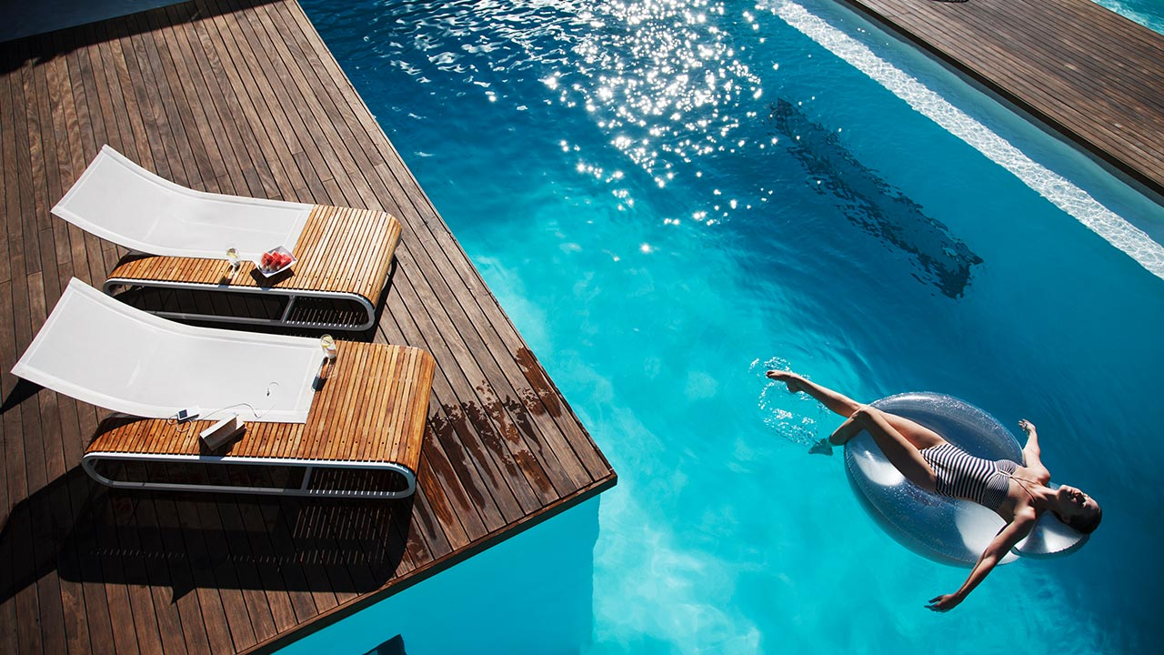 Woman floating in a luxury pool | Astro-O/Caiaimage/Getty Images