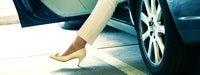 A woman&#39s foot stepping out of a vehicle with a yellow heel on 