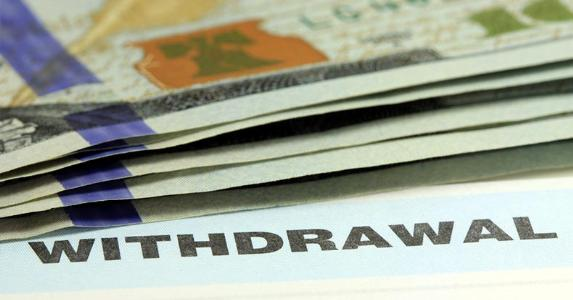 Withdrawal slip and money © larry1235/Shutterstock.com
