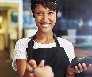 Woman holding chip card reader © Uber Images/Shutterstock.com