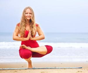 Woman doing yoga on beach © Pikoso.kz/Shutterstock.com