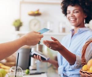 Woman handing card to cashier with chip reader   jacoblund/Getty Images