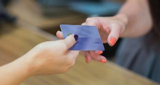 Woman handing over credit card at cash register © wavebreakmedia/Shutterstock.com