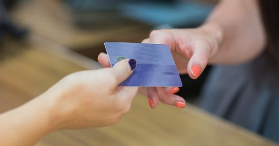 Woman handing over credit card at cash register © wavebreakmedia/Shutterstock.com