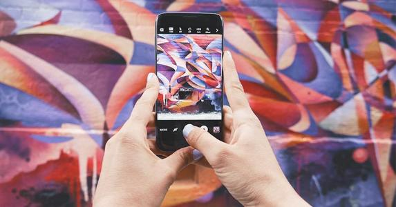 Woman holding smartphone taking photo of wall graffiti art | Patrick Tomass/Unsplash