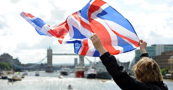 Woman holding UK flag in the air | AnadoluAgency/Getty Images