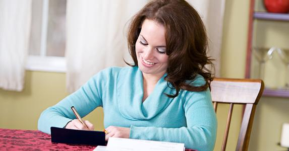 Woman in light blue longsleeve top writing checks in dining room © Sean Locke Photography/Shutterstock.com