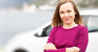 Woman standing outside car © magicinfoto/Shutterstock.com
