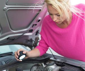 Woman in pink sweater inspecting car engine with flashlight © Matej Kastelic/Shutterstock.com