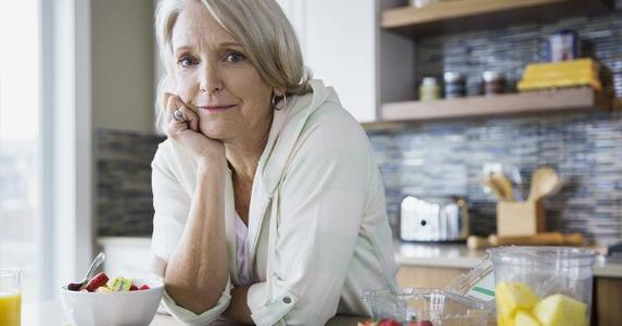 Woman leaning on kitchen counter | Hero Images/Getty Images