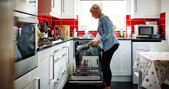 Woman loading dishwasher © iStock